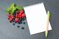 Mirtilli, lamponi, menta e blocco note per la scrittura le note o delle risoluzioni, concetto della dieta, dimagrente, disintossi Fotografie Stock