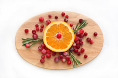 Mirtilli rossi, arancia e rosmarini sul bordo di legno Fotografia Stock