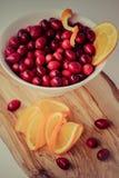 Mirtilli rossi e fette arancio succose immagini stock