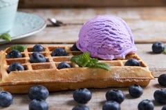 Mirtillo del gelato su una cialda belga su una superficie di legno Cialde casalinghe deliziose con il gelato di frutta fresca Est immagini stock libere da diritti