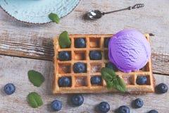 Mirtillo del gelato su una cialda belga su una superficie di legno Cialde casalinghe deliziose con il gelato di frutta fresca Est fotografie stock