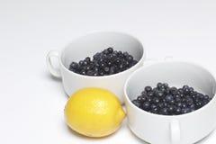Mirtillo versato nelle tazze e nel limone bianchi, taglio a metà Bugia su un fondo bianco Immagini Stock
