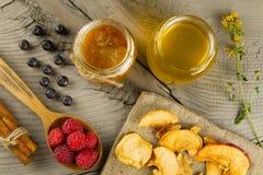 Mirtilos e framboesas com varas de canela e frascos do mel com as maçãs secadas no fundo de madeira Alimento saudável do vegetari Imagens de Stock Royalty Free