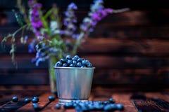 mirtilos em uma cubeta em um fundo de madeira escuro Flores do campo foto de stock royalty free