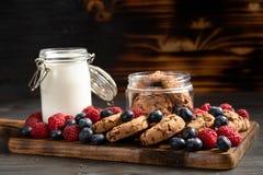 Mirtilos, framboesas e biscoitos colocados sobre a bandeja de madeira fotografia de stock royalty free