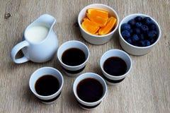 Mirtilos frescos, fatias alaranjadas, potenciômetro do leite e xícaras de café imagens de stock