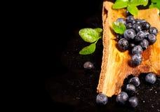 Mirtilos na cuba de madeira em uma superfície preta Fotografia de Stock Royalty Free