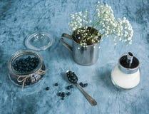 Mirtilos no frasco e nas flores Fotos de Stock Royalty Free