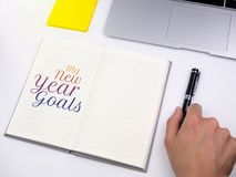 Mis metas del Año Nuevo mandan un SMS en el cuaderno con la pluma de tenencia de la mano en el escritorio Fotos de archivo