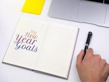 Mis metas del Año Nuevo mandan un SMS en el cuaderno con la pluma de tenencia de la mano en el escritorio Foto de archivo