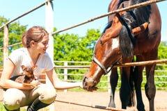 Mis tres mejores amigos Muchacha del pelirrojo que se sienta cerca de caballo Fotografía de archivo
