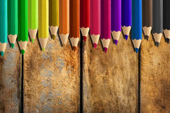 Misaligned coloured pencils on wooden desk background. Set of misaligned coloured pencils on wooden desk background Stock Photo