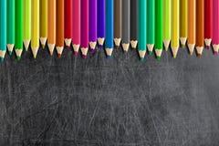 Misaligned färgade blyertspennor förbigår den svart tavlan för svart tavla arkivfoto