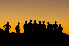 Misaligned group of people silhouettes at sunset. Misaligned silhouettes of ten people againts a yellow sky at sunset Royalty Free Stock Images