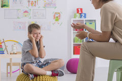 Misbehaving boy during session with a psychotherapist. Misbehaving boy sitting on a pouf during session with a psychotherapist Stock Photos