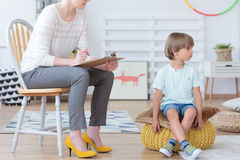 Misbehaving boy and counselor. Misbehaving boy sitting on a yellow pouf during meeting with counselor in colorful classroom Royalty Free Stock Photo