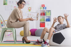 Misbehaving child sitting on a modern pouf. Talking with a women psychologist Royalty Free Stock Photography