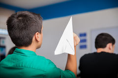 Misbehaving during class. Naughty high school student throwing a paper plane during class Stock Image