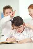 Misbehaving classmates. Two little children pulling about their classmate in classroom Stock Image