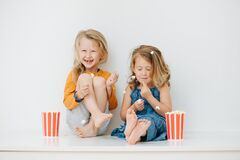 Misbehaving Siblings Sitting On A Table With Their Legs Up. Over White Wall Stock Photos