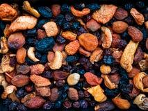 Miscela dei frutti e dei dadi asciutti, prugne, albicocche secche, mele, uva passa, fondo immagini stock