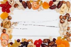 Miscela dei frutti e dei dadi secchi su un fondo di legno d'annata bianco con lo spazio della copia Vista superiore Simboli della immagine stock