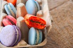 Miscela dei macarons variopinti in un contenitore dell'uovo della carta del mestiere Fotografia Stock