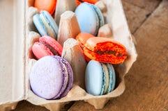 Miscela dei macarons variopinti in un contenitore dell'uovo della carta del mestiere su un corteggiare Fotografia Stock Libera da Diritti