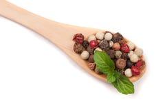 Miscela dei peperoni caldi, rossi, neri, del bianco e del peperone verde in un cucchiaio di legno isolato su fondo bianco Vista s Fotografia Stock Libera da Diritti