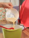 Miscela del latte e dell'uovo aggiunta Fotografie Stock