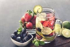 Miscela dell'acqua infusa Flavored della frutta fresca della fragola, uva e Fotografia Stock