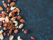 Miscela dell'anacardio, pecan, pinoli, nocciole sul blu Fotografia Stock Libera da Diritti