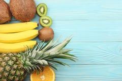 miscela della noce di cocco, della banana, del kiwi, dell'arancia e dell'ananas freschi su fondo di legno blu Vista superiore con immagini stock libere da diritti