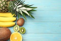 miscela della noce di cocco, della banana, del kiwi, dell'arancia e dell'ananas freschi su fondo di legno blu Vista superiore con immagine stock libera da diritti