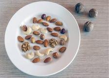 Miscela delle mandorle, delle nocciole, delle noci, degli anacardi su un piatto bianco e di tre intere noci sulla superficie di l immagini stock