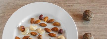 Miscela delle mandorle, delle nocciole, delle noci, degli anacardi su un piatto bianco e di tre intere noci sulla superficie di l fotografia stock