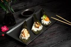 Miscela di Temaki con il salmone, l'anguilla ed il gamberetto su un fondo di legno scuro immagini stock