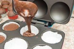Miscela di versamento del bigné del cioccolato nel modellato in Immagini Stock
