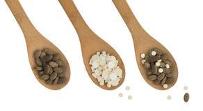Miscela farmaceutica delle pillole e delle compresse della medicina sui cucchiai di legno Immagine Stock