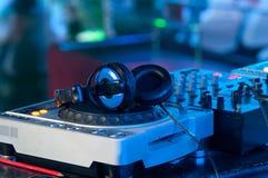 Miscelatore del DJ con le cuffie ad un locale notturno Fotografia Stock