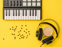 Miscelatore di musica, chicchi di caffè sparsi, cuffie e una tazza di caffè su un fondo giallo La vista dalla parte superiore immagini stock libere da diritti
