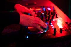 Miscelatore di musica del DJ delle mani sul partito nel night-club Fotografie Stock Libere da Diritti