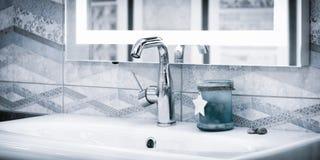 Miscelatore moderno di lusso del rubinetto di stile su un lavandino rotondo bianco nella bella insegna blu-chiaro di web del bagn fotografia stock