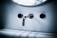 Miscelatore moderno di lusso del rubinetto di stile su un lavandino rotondo bianco nella bella insegna blu-chiaro di web del bagn immagini stock libere da diritti