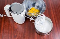 Miscelatore tenuto in mano elettrico, uova battute ed uova rotte in ciotola fotografie stock