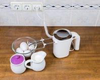 Miscelatore, uova, zucchero e crema tenuti in mano elettrici sulla tavola immagini stock libere da diritti
