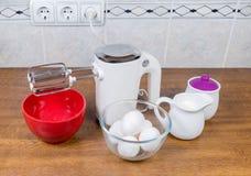 Miscelatore, uova, zucchero e crema tenuti in mano elettrici sulla tavola fotografia stock libera da diritti
