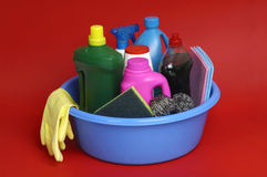 Miscellaneous cleaning inside a blue cube. Miscellaneous cleaning products in a blue bucket and a red backgr stock images