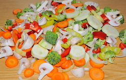 Miscellaneous fresh vegetables cut up in pieces ready for stir f. Ry or saute. It includes carrots, broccoli, onions, asparagus, squash, and red and green pepper Stock Photography