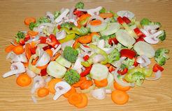 Miscellaneous fresh vegetables cut up in pieces ready for stir f. Ry or saute. It includes carrots, broccoli, onions, asparagus, squash, and red and green pepper Stock Images